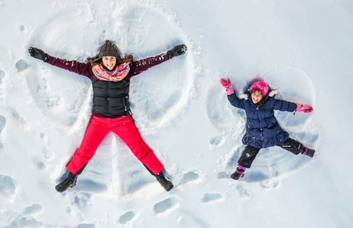 women with her girl laying down on snow
